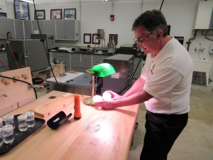 Bruce Hart, manager of Saginaw Valley State University's Independent Testing Lab, shows new epoxy samples from Gougeon Brothers Inc. in Bay City that are intended for use on surfboards.