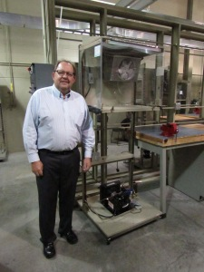 Doug Zentz, associate professor and program chair of Ferris State's HVACR department, poses with a miniature refrigerator that all freshman students are required to build.